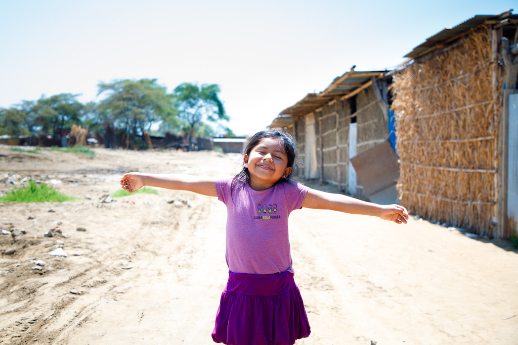 A young Peruvian girl stands in a road with her arms open wide and a smile on her face.
