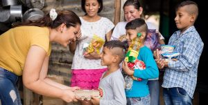 An adult woman bends down to give a care package to a young, Venezualen boy. His family looks on and smiles.