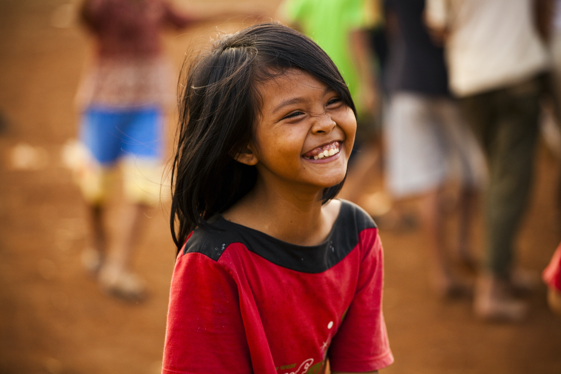 A young girl in a red shirt, laughing.