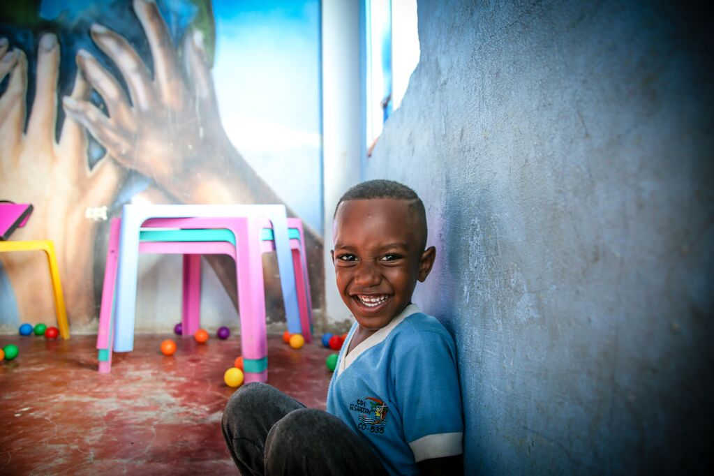 Little boy in a blue shirt sits against the wall of his Compassion centre and beams.