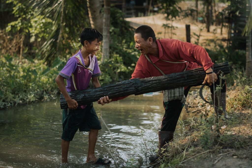Oosamai and his son, Gungamae-ou lift a log out of the river together while laughing.