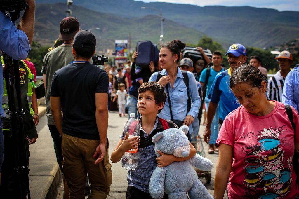 Little boy holding a teddy bear crossing the border