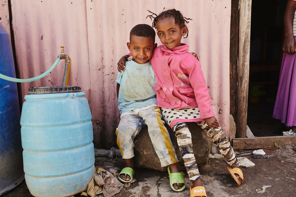 One little girl and one little boy smile with their arms around eachother beside a rainwater filter.