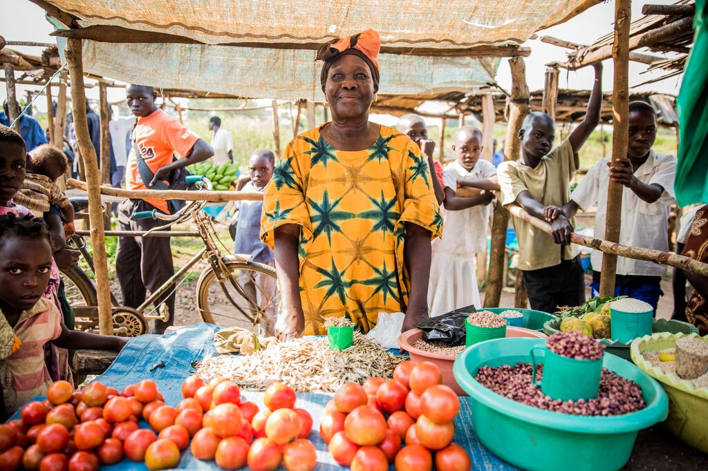 A Ugandan woman stands in front of her stad of vegetable seeds and tomatoes