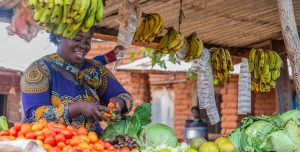 A Tanzanian woman stands at her produce stall in a market place. She's selling mounds of tomatos, bananas, lettuce and other fruits and vegetables.