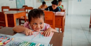An Indonesian toddler sits in a classroom and colors on a piece of paper.