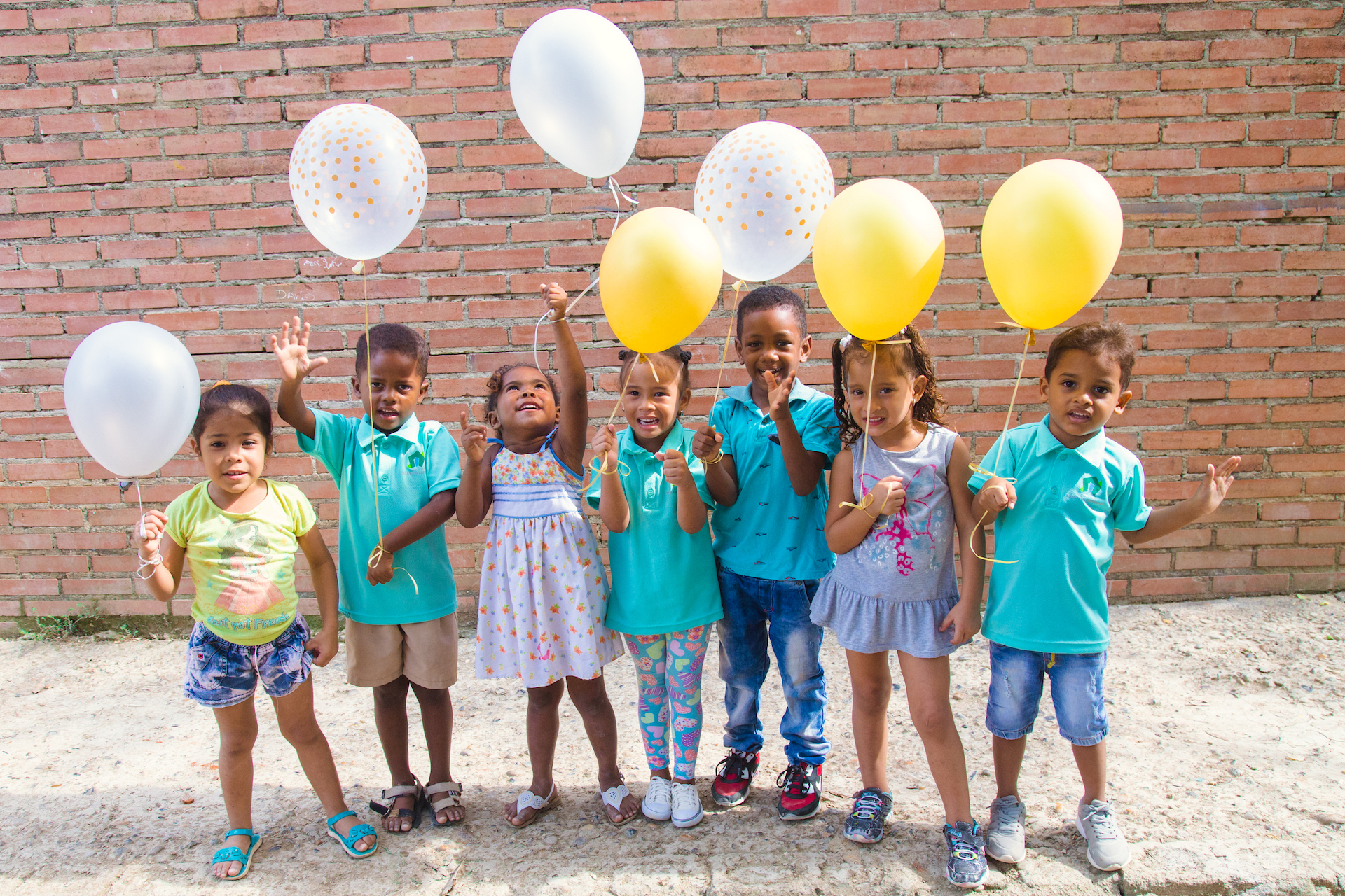 A group of children standing in a row holding yellow and white balloons.