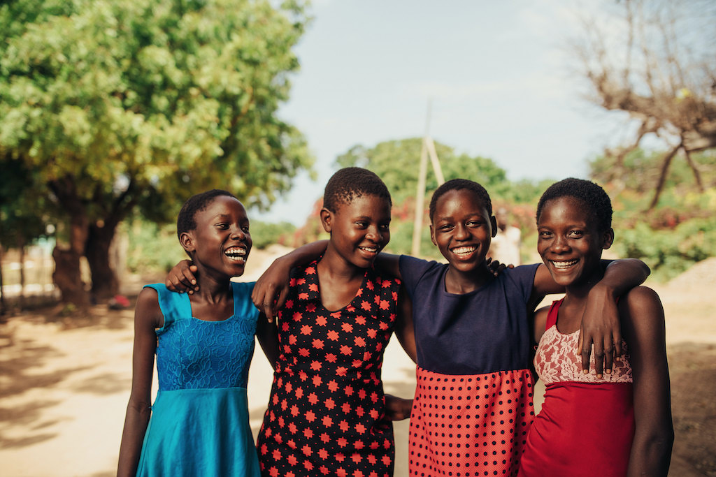 A group of four teen girls with their arms around each other.