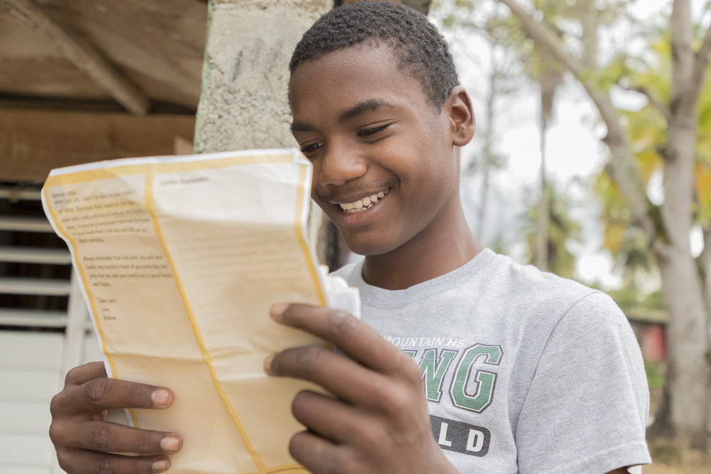 Julio reading a letter while smiling.