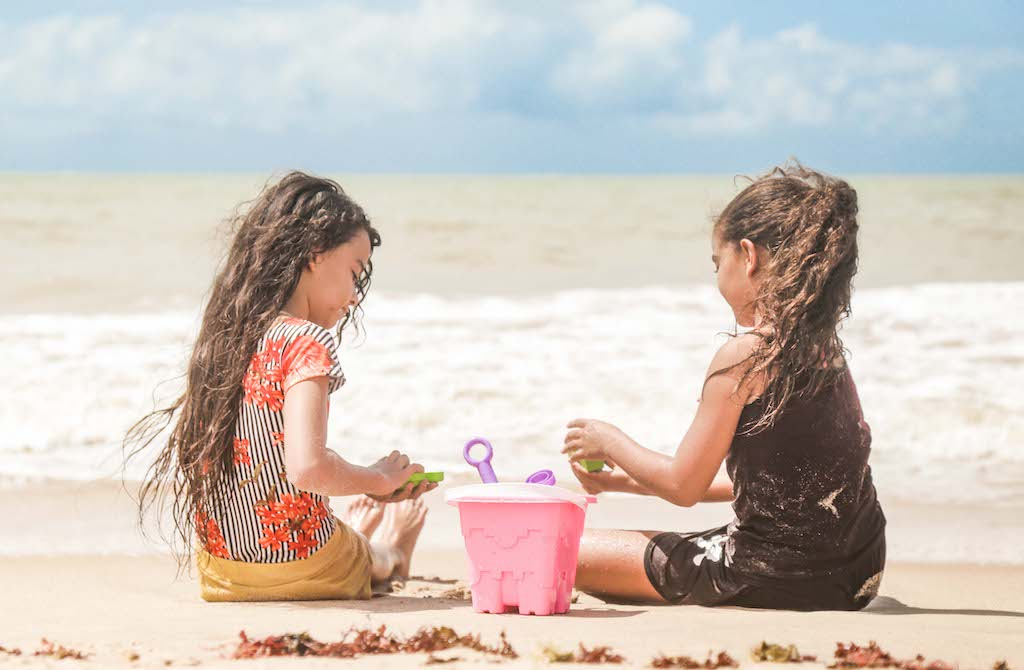 Two young girls play with a pink bucket in the sand at the beach.