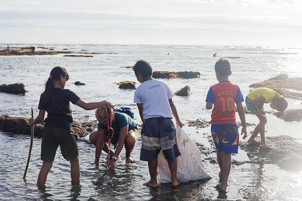 Four kids hold garbage bags while wading into the shore of a beach.