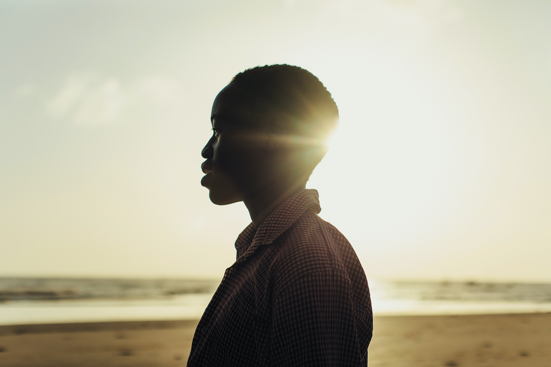 A silhouetted photo of a young Kenyan woman at sunset on a beach.