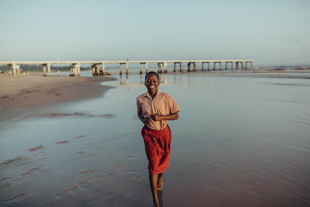 A young woman runs along the shore of a beach.