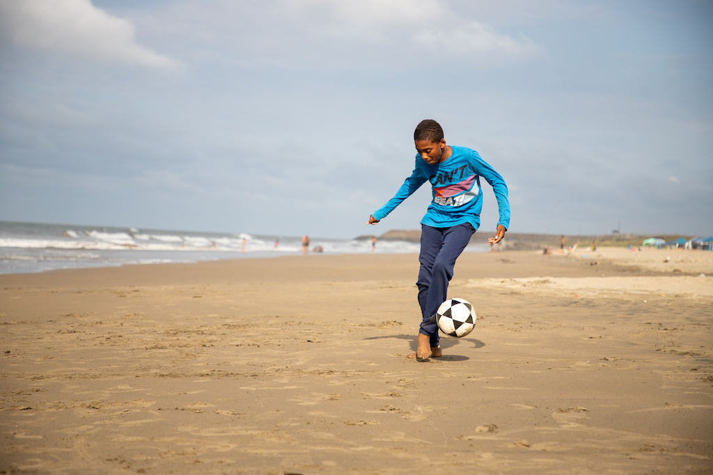 A boy kicks a soccer ball on a beach.