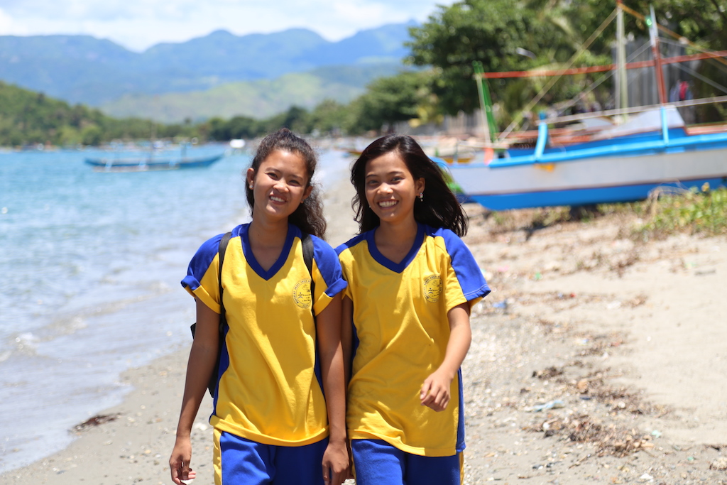 Two teen girls walking on a beach.