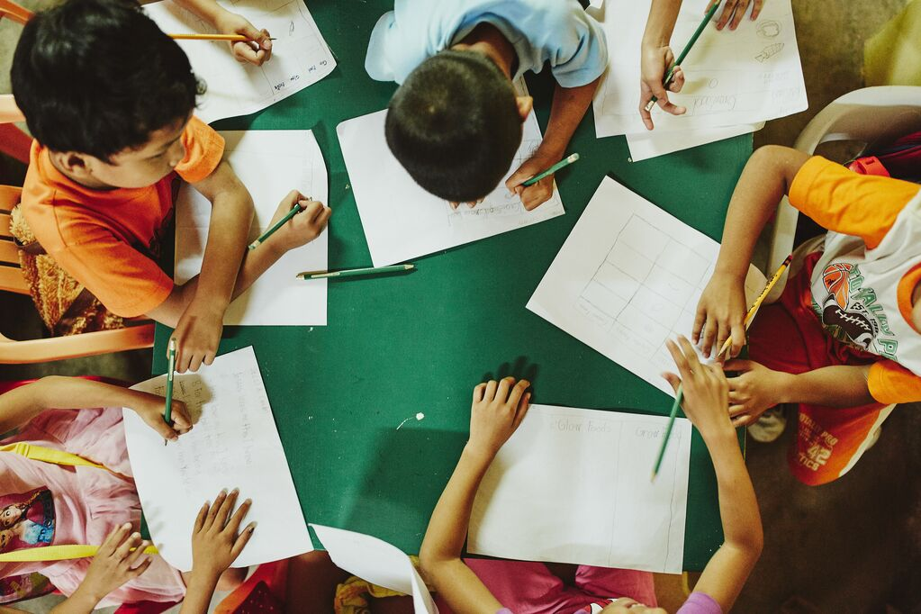 Kids sit at a table and write on paper. Picture is bird's eye view.