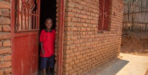 A boy in a red shirt stands in the door of a brick building and smiles.