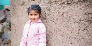 A little girl, wearing a pink jacket, stands in front of concrete wall and smiles, shyly.