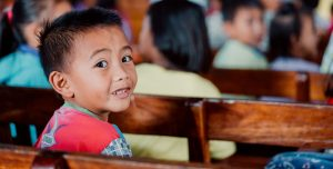An young Indonesian boy sits on a classroom bench. He looks back towards the camera.