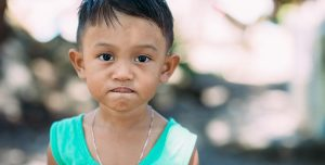 A young Phillippino child, wearing a turquois tank top, looks at the camera and sucks on his lower lip..