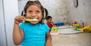A little girl, wearing a blue shirt, smiles proudly and brushes her teath