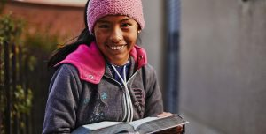 A middle school aged girl holds and open Bible. She stands outside a cement building and smiles.