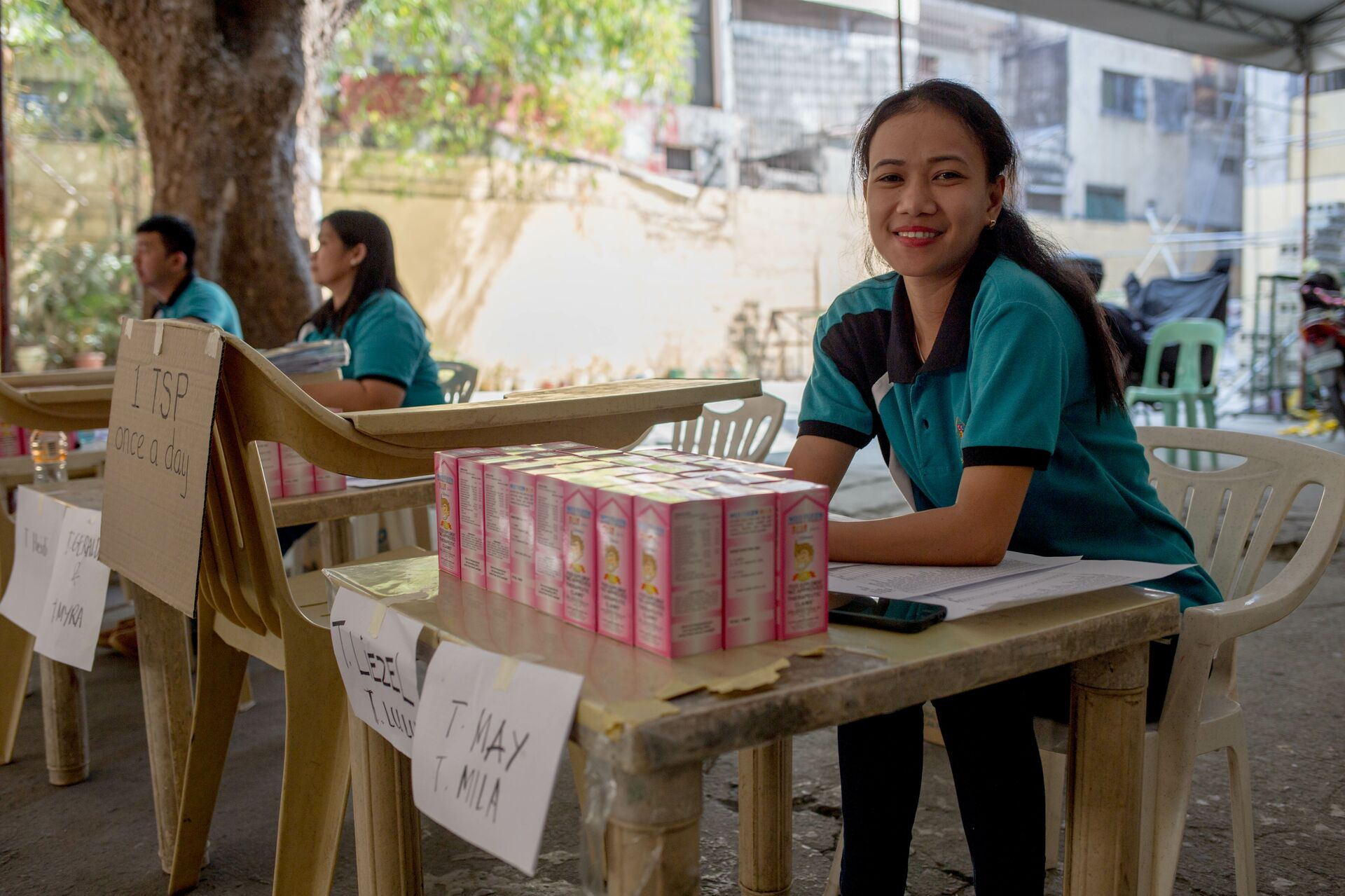 A Compassion Centre staff member sits at a table with packs of vitamins in front of her, ready to distribute to Compassion-assisted families.