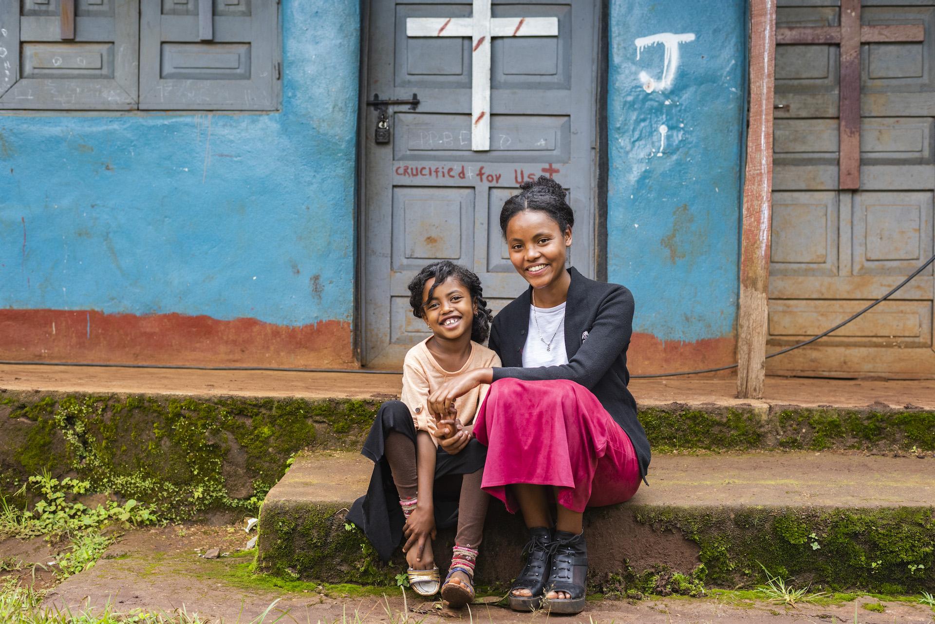 Sosina and Deborah sitting on the step of a church.
