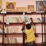 a child reaches for a book on a bookshelf.