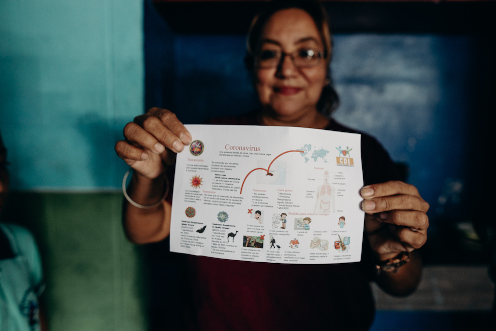 A Compassion staff member displays an example of a Coronavirus information card.