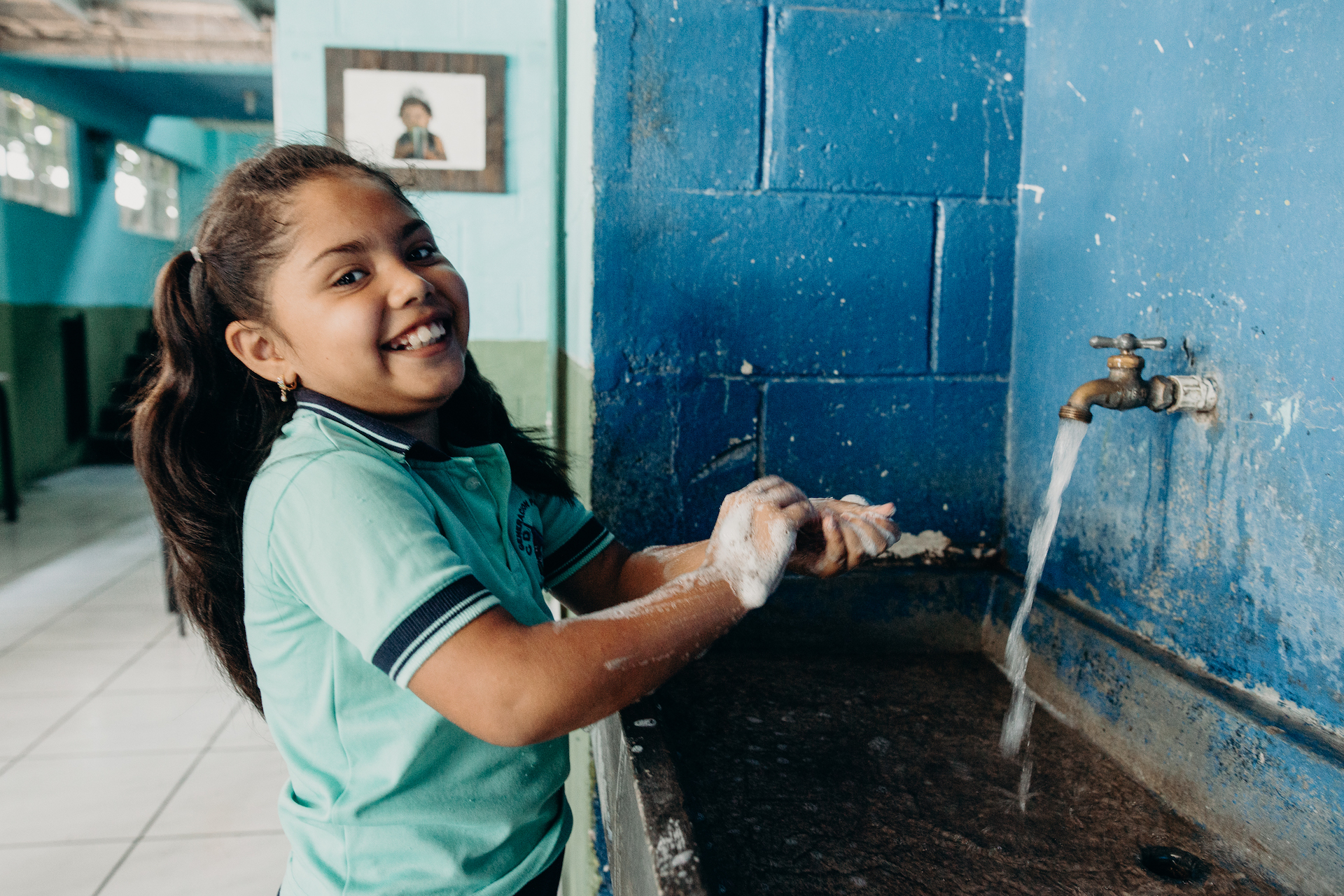 A girl washing her hands at a sink in El Salvador