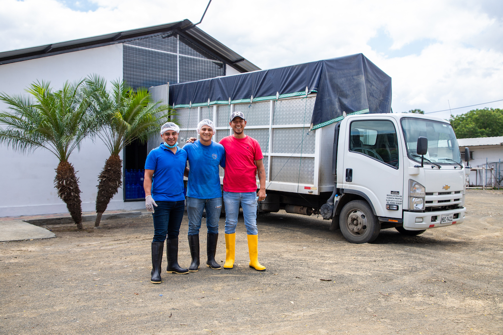 Leonardo, Joel and Cristian pose in front of a truck parked in front of the water plant.
