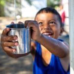A young boy, Jimmy, reaches out to fill a cup with clean water.