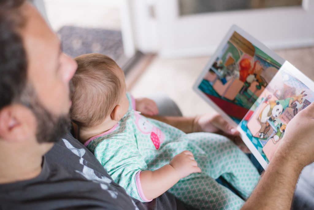 A man reading a picture book to an infant.
