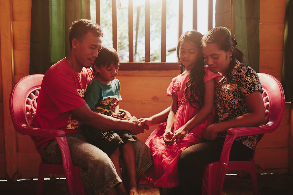 A family praying together in their home.