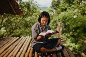 A girl sits outside reading her Bible.
