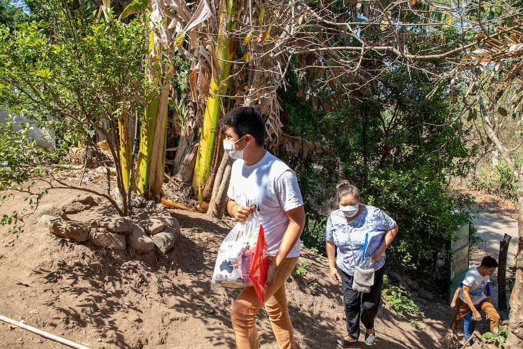 A group of volunteers walks up a steep hill with groceries. They are wearing masks.