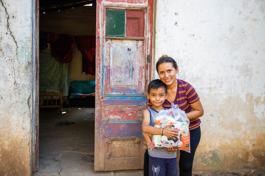 Kirian and her son in front of their home with a bag of groceries.