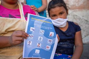 A girl wearing a mask sits next to her mother who is holding a pamphlet about COVID-19 prevention.