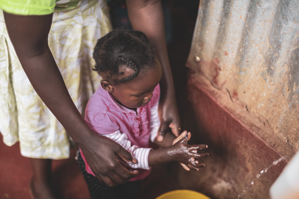 A young toddler girl washes her hands with the help of her mother.