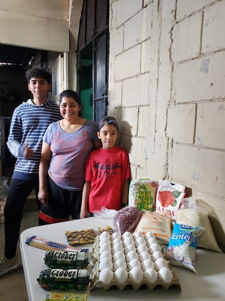 A family poses in front of a table of groceries delivered by Compassion staff.