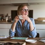 Smiling female entrepreneur looking through a window while drinking coffee and working at a table in her kitchen