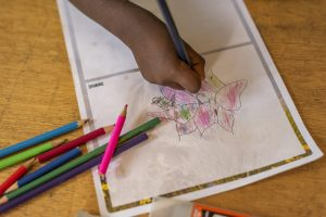 A child's hand drawing a picture.