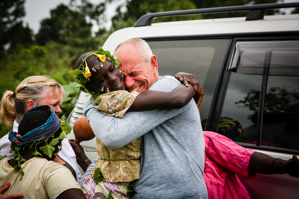 Violet, who is wearing traditional dress gives her sponsor a big hug, as the sponsor cries of joy