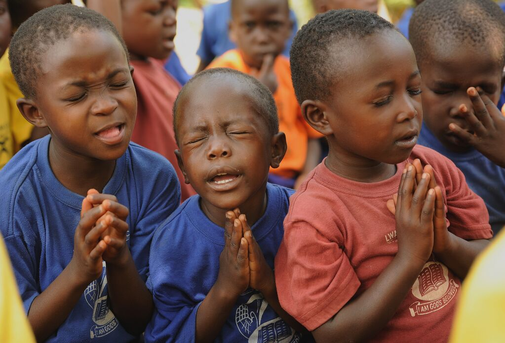 3 boys praying, one is squeezing his eyes closed very tightly