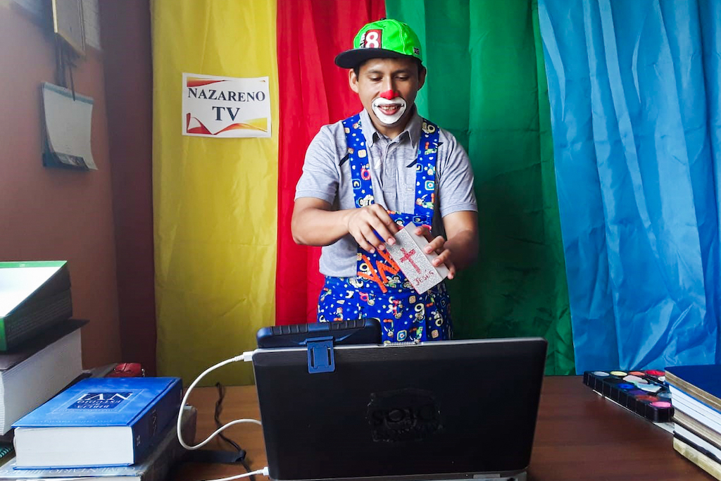 Pastor Alex stands in front of a webcam, dressed as a clown.