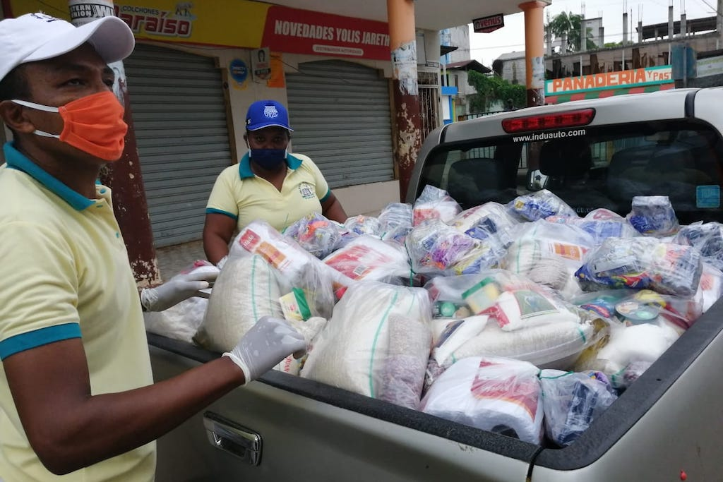 Two staff members load bags of groceries and supplies onto the bed of a pick-up truck.