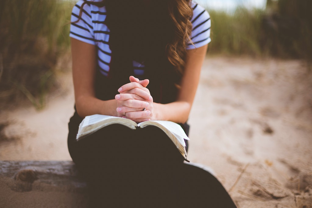 A woman with her hands folded on an open book.