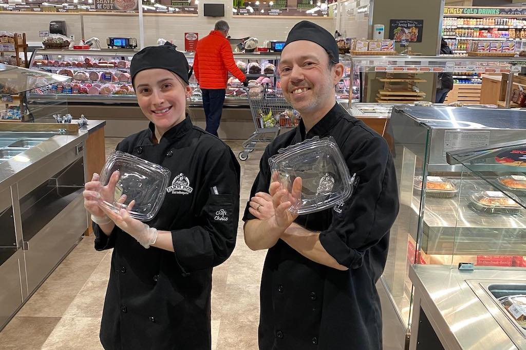 Two grocery store employees stand with takeout containers.