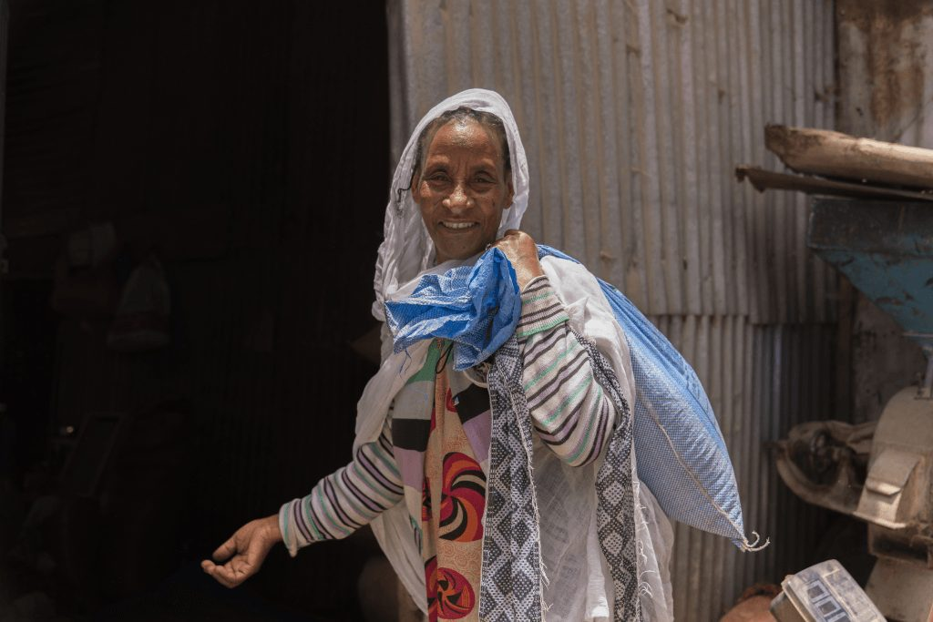 A woman carrying a bag of rice.